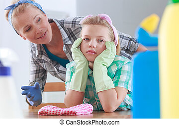 Girl with rubber gloves sitting at a table - Sad girl with...