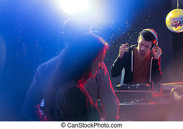 Deejay at turntable giving concert at nightclub