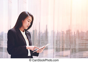 Elegant young business woman using tablet by the window for relax, looking at screen and Business District blurred background
