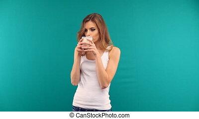 beautiful girl drinking yogurt milk from a glass on a green...