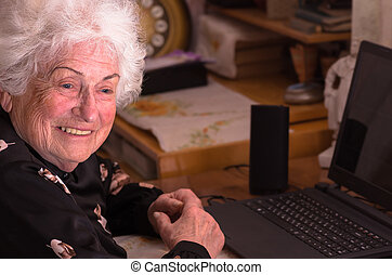 Happy grandmother sits at the computer - Happy grandmother...