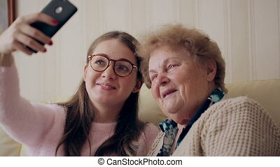 Granny and young girl making self photos on mobile or smart phone while sitting on sofa or couch at home. Happy ladies making funny faces for camera.