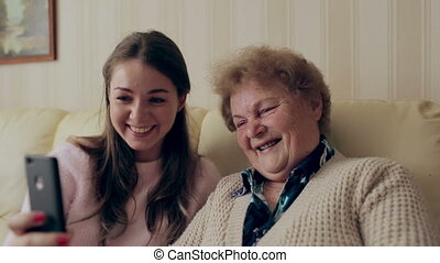 Beautiful grandmother and daughter are doing selfie and smiling while sitting on couch at home.