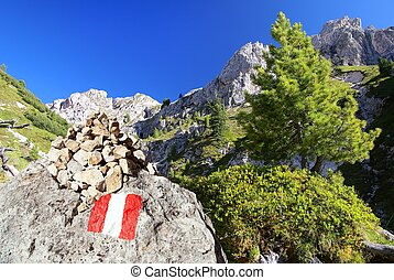 Tourist sign and stone pyramid in Dolomites alps mountains,...