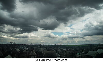 Storm Clouds in the Sky are Moving over the Houses of the City. Time Lapse