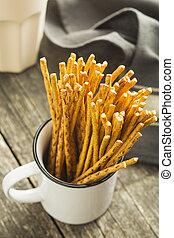 Salty pretzel sticks. - Salty pretzel sticks in white cup.