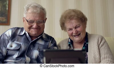 Mature senior couple enjoying modern technology using tablet pc. Elderly people communicating with internet at home.