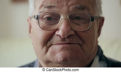 Portrait of Old Man. Grandfather with glasses looks at the camera and smiles.
