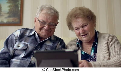 Senior couple in sofa using electronic tab. A cheerful senior couple having a video chat on a digital tablet.