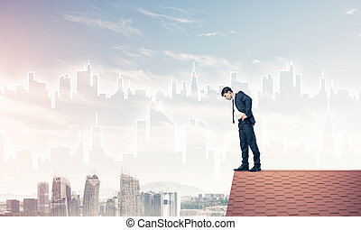 Businessman looking down from roof and modern cityscape at...