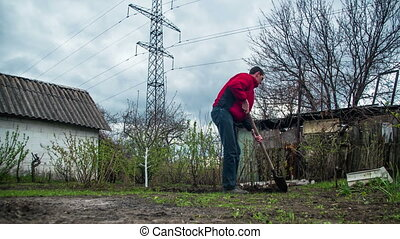 Young Man Gardener Digs the Ground with a Shovel in the...
