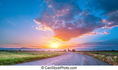 Beautiful countryside road at sunset. Colorful clouds sky,...