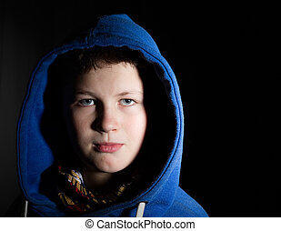 Portrait of a teenager in a hood on black background