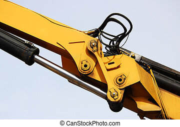 The device of a yellow loader on the railway. Hydraulic system against the sky.