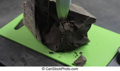 piece of cocoa beans is cut with a knife.
