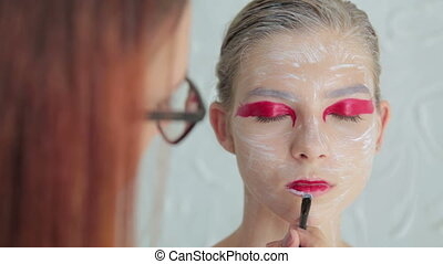Lips painting: professional make-up artist making face...