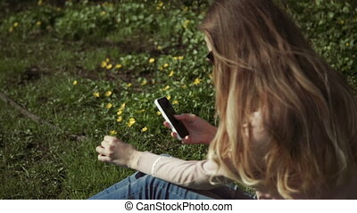 Beautiful young woman in jeans sitting happily in lush green grass in a summer park under sunlit trees