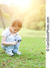 Kid exploring nature with magnifier glass at outdoors. -...