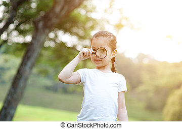 Asian little girl exploring nature with magnifier glass at outdoors.
