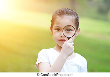 Asian little girl with magnifier glass at outdoors.