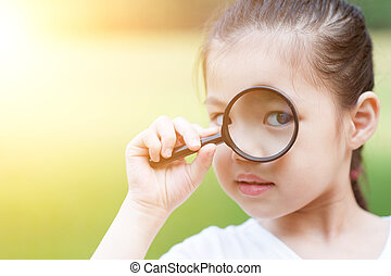 Asian child with magnifier glass at outdoors. - Portrait of...