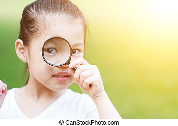 Asian kid with magnifier glass at outdoors. - Portrait of...