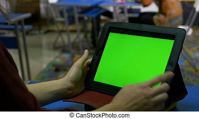Female hands touching the green screen of a tablet pc on a desk