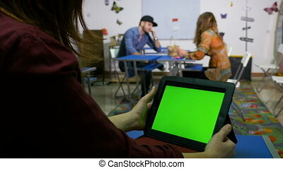 Teenagers in classroom socializing with green screen tablet...