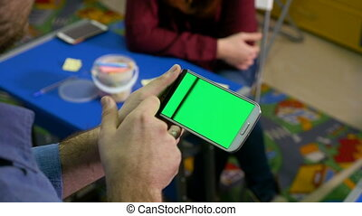 Group of people brainstorming in a workshop and man holding smartphone with green screen