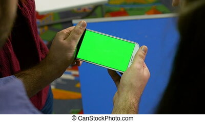 Man holding smart phone with green screen and presenting in...