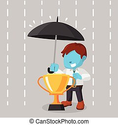 blue businessman covering trophy with umbrella