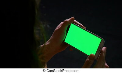 Woman using smart phone and making swipe zoom in and out...
