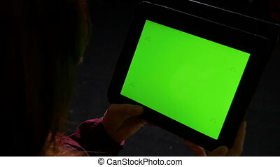 Young woman at using tablet pc late in the night and doing...