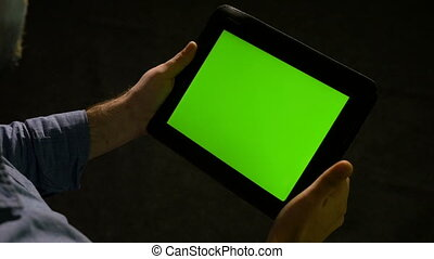 Man using tablet pc with green screen and zooming in and out...