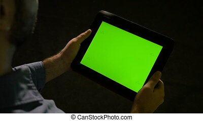 Man browsing on a tablet pc with green screen