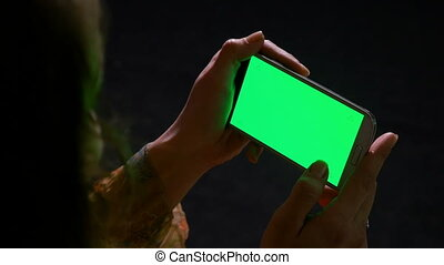 Hands of a woman surfing the internet on a green screen...