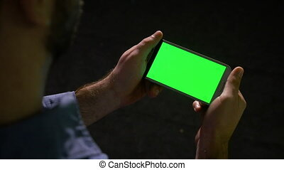 Young business man using green screen smart phone to check...
