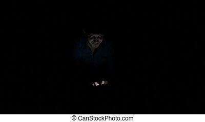 Man alone in the dark texting on smartphone