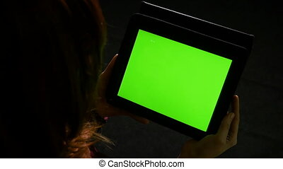 Teenager girl reading online content on tablet pc with green...