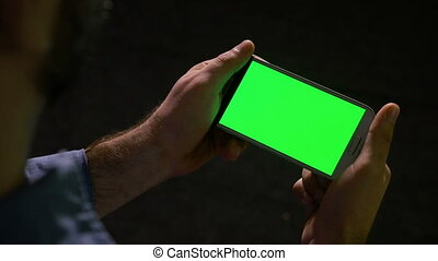 Man watching media content on smart phone with green screen