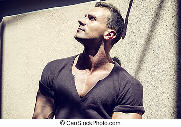 Handsome muscular young man outdoor, leaning against wall...