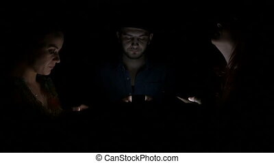 Two young women and man in the dark using their smart phones...