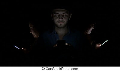 Three young people using their smart phones in the dark instead of spending time together