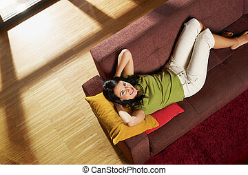 woman on sofa - Woman lying down on sofa in her new house...