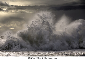 Stormy sea wave splash at sunset