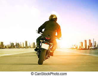rear view of man riding motorcycle on urban traffic road for...