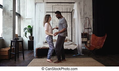 Multiethnic couple dancing in pajamas. African male and...