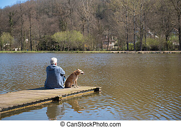 Man with dog on landing stage - Man sitting with his dog on...