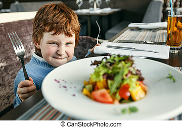 Red haired boy with forks eating salad - Little red haired...