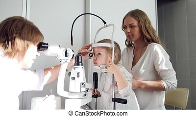 Child's ophthalmologist checks little girl's eyesight -...